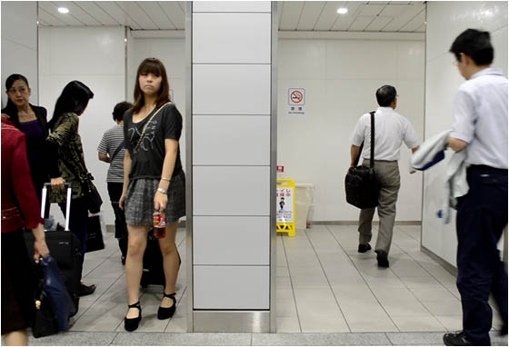 Slim men and women walking in and out of the Kyoto train station toilet